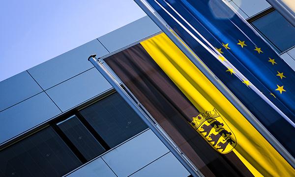 Bild eines Gebäudes und im Vordergrund die EU-Flagge und die Flagge von Baden-Württemberg