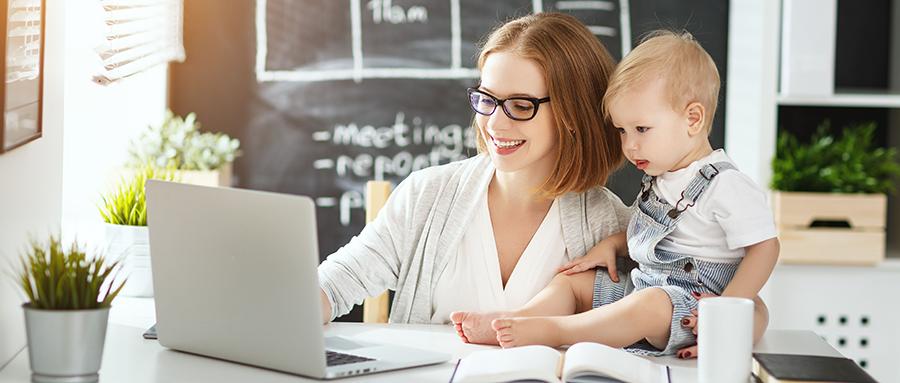 Eine Frau mit Brille sitzt mit ihrem kleinen Sohn vor dem Laptop